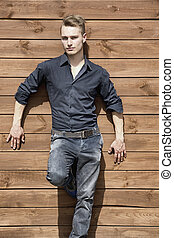 Handsome blond young man standing outside against wood wall