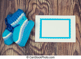 knitted baby socks and blank note on wooden background