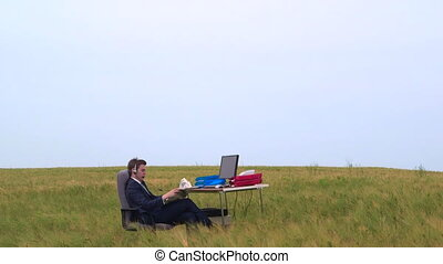 Business person reading newspaper at office desk in a green field