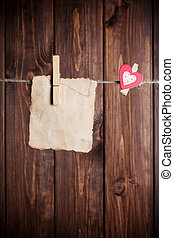 old paper sheet and small paper heart hanging on clothesline...