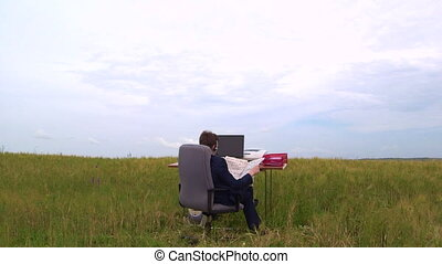 Business man takes break and reads newspaper at office desk in a open air