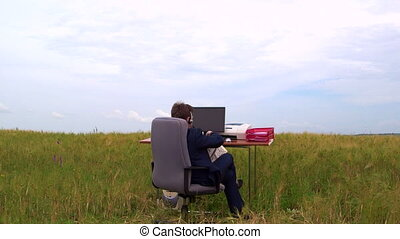 Business man taking a break at office desk outside rear view