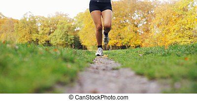 Young woman jogging in park - Low section image of young...