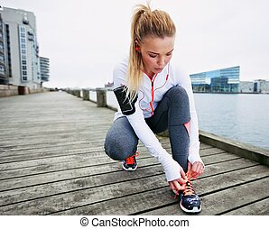 Fastening her shoelaces before the run - Fit and sporty...