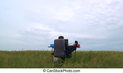 Business man relaxing at office desk in a green field