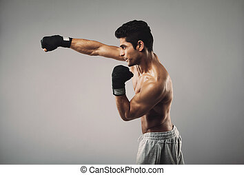 Young man practicing shadowboxing on grey background -...