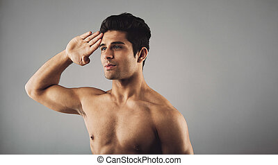 Young muscular man saluting - Portrait of young muscular man...