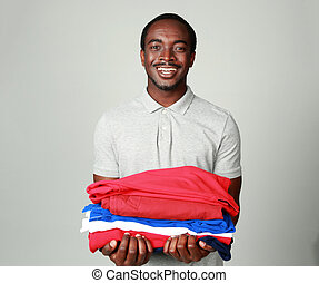 Portrait of a smiling african man holding his clothes on...