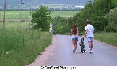 Young couple with bicycle walking down a country road