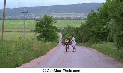 Young girl learning to ride bicycle on a country road -...