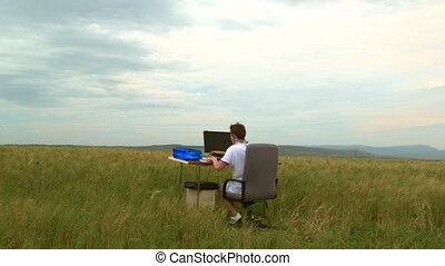 Teenager using desktop computer outdoors