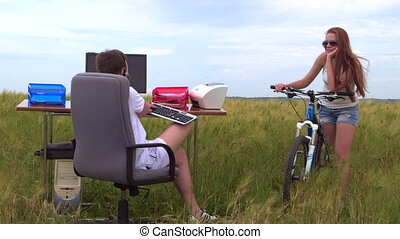 Young girl with bicycle looking at the guy behind a computer in field