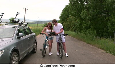Young couple with bicycles near his car looking at map on tablet computer