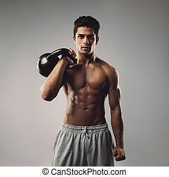 Strong young man working out with kettle bell - Portrait of...