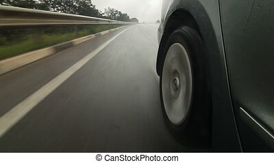 Car speeding along wet highway in heavy rain