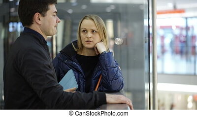 Man and woman discussing something in trade center - Young...