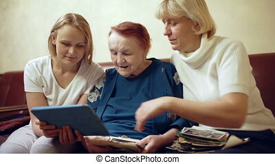 Family of three women looking photos on touchpad - Dolly...