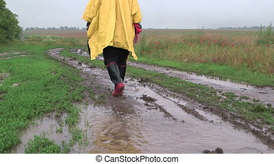 Man goes on a dirt country road through the field in rain -...