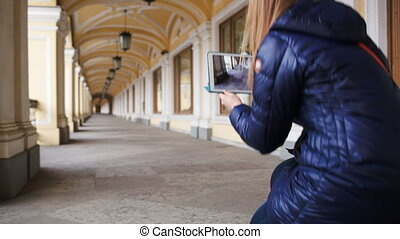 Woman with tablet PC making photo of hall in perspective -...