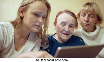 Woman with pad showing photos or video to her mother and grandmother