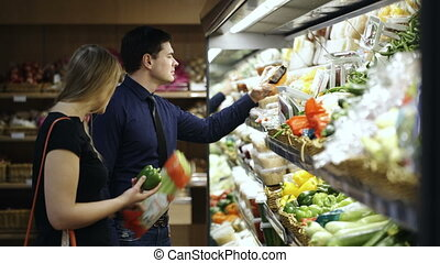 Young couple choosing fresh vegetables in supermarket -...