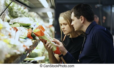 Man and woman buying fresh vegetables in grocery - Young man...