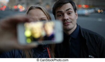 Young couple with phone having fun while taking pictures -...
