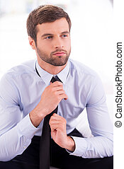 Businessman tying a necktie. Thoughtful young businessman...