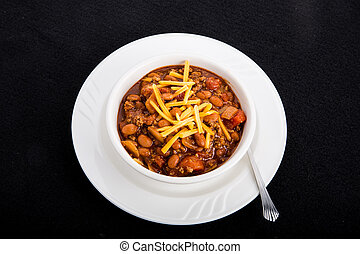White Bowl of Chili with Beans and Cheese on Black Background