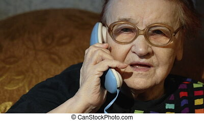 Elderly woman in glasses taking a call - Dolly close-up shot...