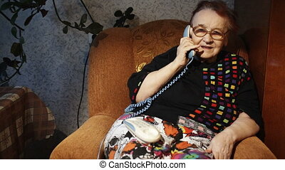 Old woman receiving a phone call in the evening - Dolly shot...