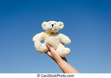 fluffy teddy bear in hand on blue sky background - small...