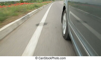 Wheel car racing down the highway along road surface markings