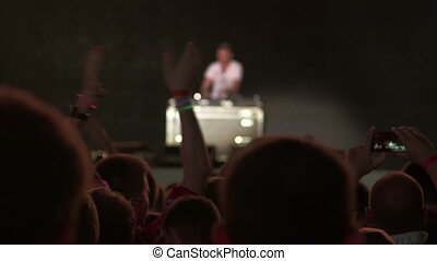 Dj mixing music on the deck in front of a crowd on stage