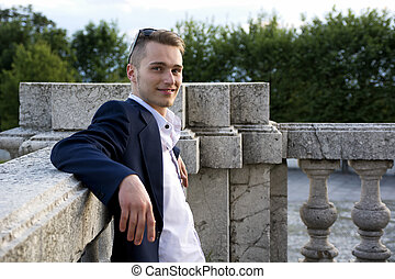 Handsome blond young man on marble banister smiling at...