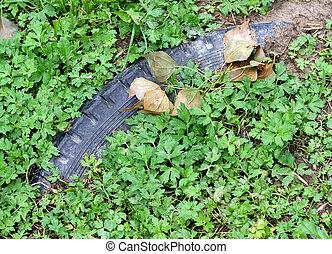 black tyre submerged by green vegetation 1 - pollutant black...