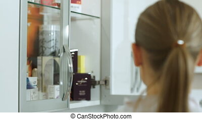 Cosmetician taking cosmetic from cabinet and showing it her...
