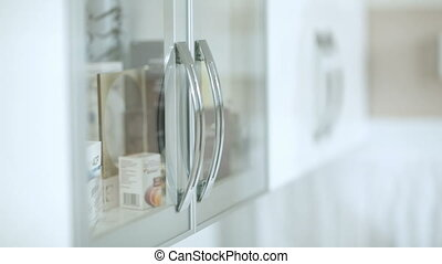 Cosmetician taking a cosmetic from cabinet and checking information on it