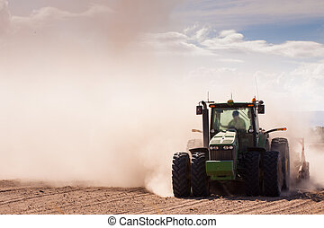 Tractor in a dusty dry farm - Close-up of a tractor plowing...