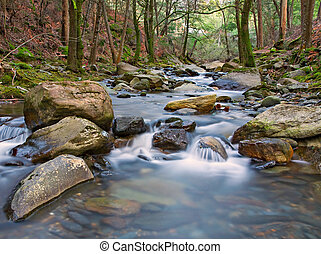 Flowing River - Beautiful view over a river flowing through...