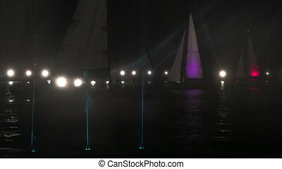 Holiday light show and sailing yachts in water area of Yalta
