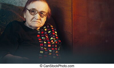 Elderly woman in glasses watching TV and changing channels -...