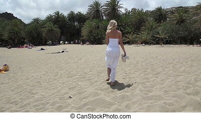 women on the beach with palm trees