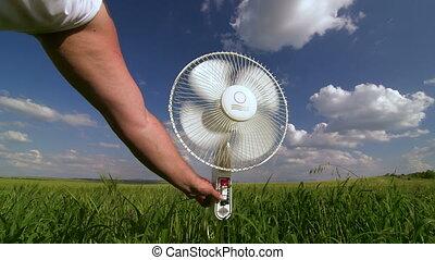 Floor electric fan turned on in green field