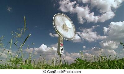 Household electric floor fan blowing in green field