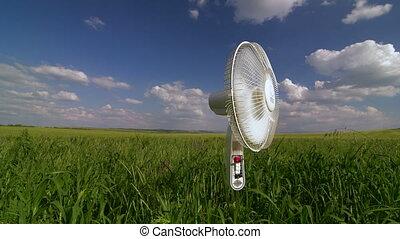 Floor electric fan standing in green field