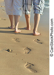 Legs of couple walking on beach closeup