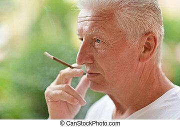 man smoking cigarette - elderly man smokes a cigarette...