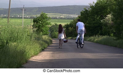 Teenage couple with bicycle on a country road