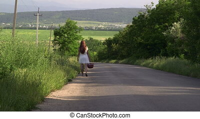 Young girl with basket walking along a country road rear...
